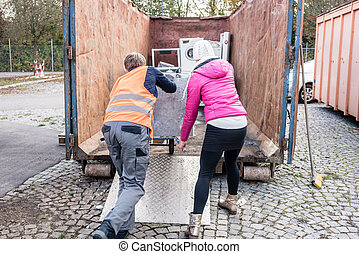 Woman and man giving electrical appliances to recycling...