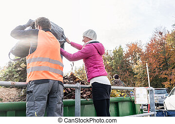 Woman and man giving waste green in container on recycling...
