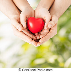 woman and man hands with heart - family and love concept -...