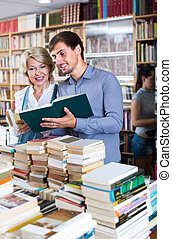 woman and man having books - cheerful mature woman and young...