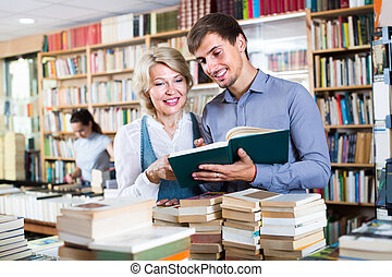 woman and man having books - cheerful woman and young man ...
