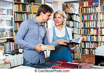 woman and man having books - family having books in hands in...