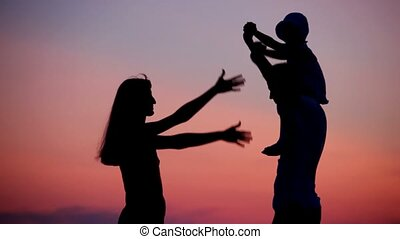 woman and man holding little girl on shoulders has fun on sunset background