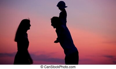 woman and man holding little girl on shoulders kissing on sunset background