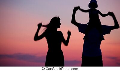 woman and man holding little girl on shoulders dancing on sunset background