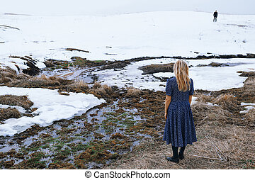 Woman and man in the winter landscape with marshy puddle