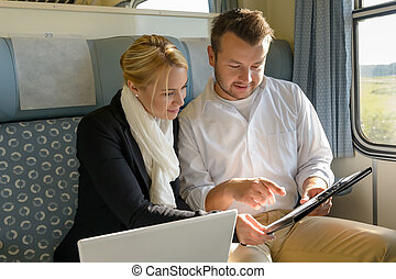 Woman and man in train laptop clipboard