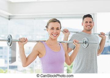 Woman and man lifting barbells at fitness studio
