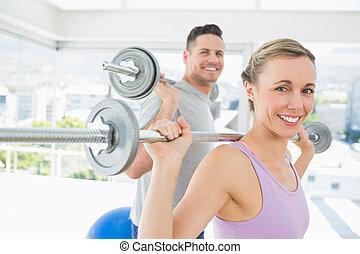 Woman and man lifting barbells