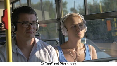 Woman and man listening music in headset during bus trip -...