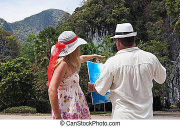 woman and man looking at the map on a tropical landscape