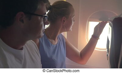 Woman and man looking out plane window