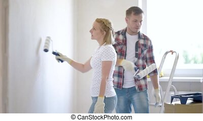 Woman and man makes repairs - Young family makes repairs in...