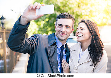 Woman and man making selfie photo outdoors