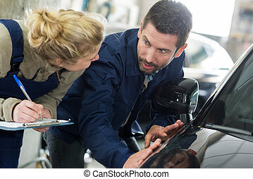 woman and man mechanic checking a car