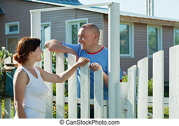 woman and man near fence wicket - Young woman and man near...