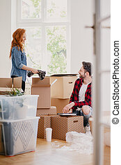 Woman and man packing stuff into carton boxes while moving out from the home