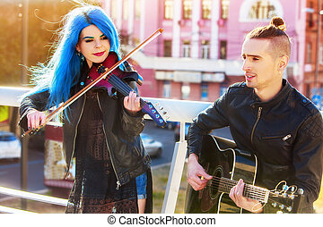 Woman and man perform music on violin city outdoor.