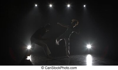 Woman and man practicing capoeira in darkness against...