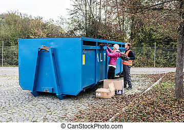 Woman and man putting waste paper in container at recycling...