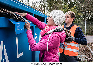 Woman and man putting waste paper in container on recycling...