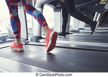 Woman and man running on treadmill at gym