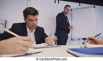 Woman and man sitting in modern office and making notes in...