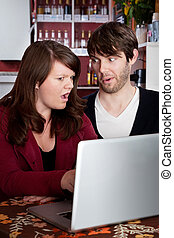 Woman and man staring in disbelief at a computer laptop