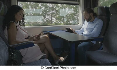 Woman and man traveling on train being non communicative...