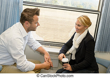 Woman and man traveling with train talking