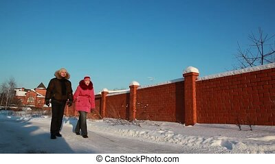 Woman and man walking outdoors at winter, house