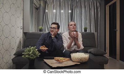 Woman and man watching tv together at home - Young adult...