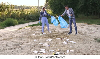 Woman and man wearing gloves are cleaning the beach in the Park by the lake.