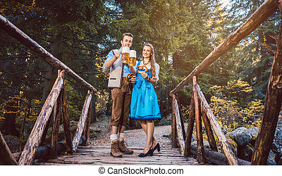 Woman and man with beer standing on bridge in Bavaria