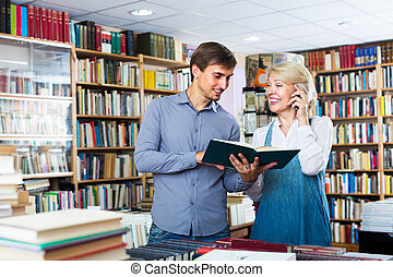woman and man with books and phone - cheerful mature woman ...
