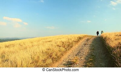 Woman and man with dog having autumn walk on a path covered...