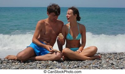 woman and man with sea stars sits on pebble beach, sea in background