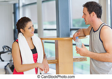 Woman and man with water bottle chatting at gym