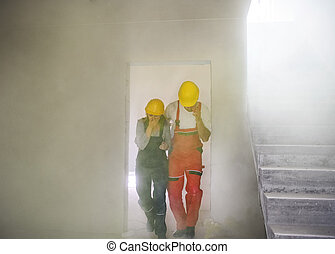 Woman and man workers suffocating at the construction site.