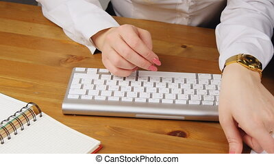woman and man working in an office typing on the keyboard