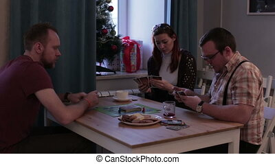 Woman and men playing a board game with cards