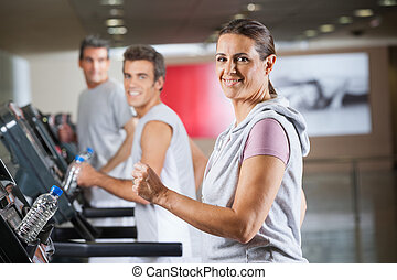 Woman And Men Running On Treadmill In Fitness Center -...