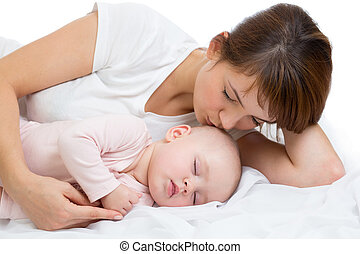 Woman and newborn boy relax in a white bedroom. Young mother kissing her newborn child. Mom nursing baby.