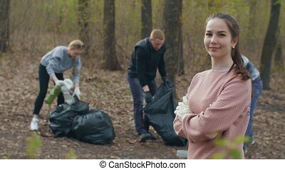 Woman and people collecting garbage on background - Young ...