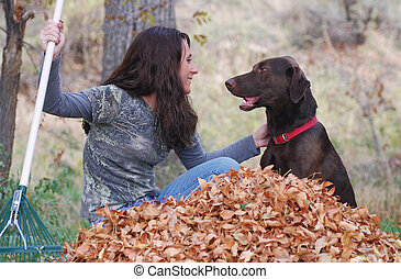 Woman raking autumn leaves with her pet dog.
