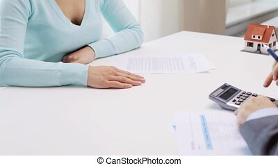 woman and realtor counting on calculator - business, real...