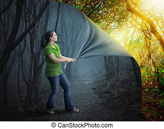 A woman pulls back a dark forest into a beautiful sunset.