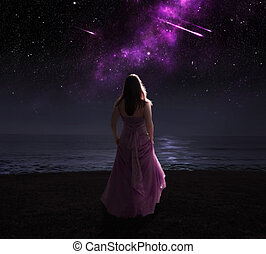 Woman and shooting stars. - Woman standing in dress at night...