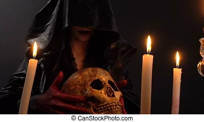 Woman and skull among candles - Footage of woman during...