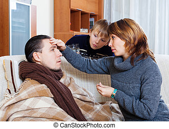 Woman and son caring for unwell man